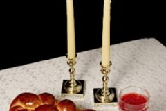 Challah, candlesticks, wine on white tablecloth
